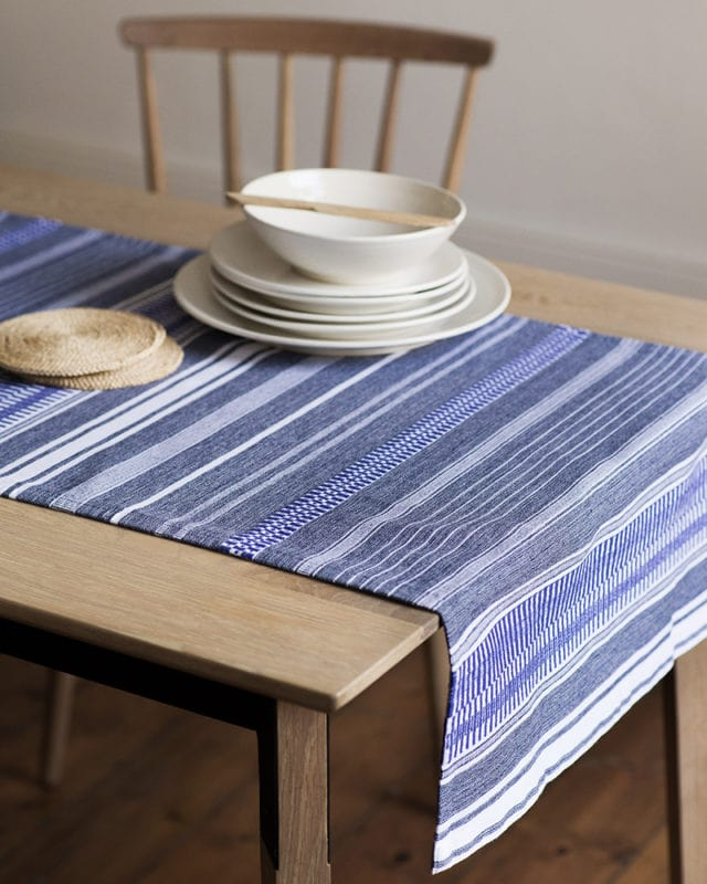 Mungo Table Linen Mali Table Runner in rolled denim is available in multiple lengths online.