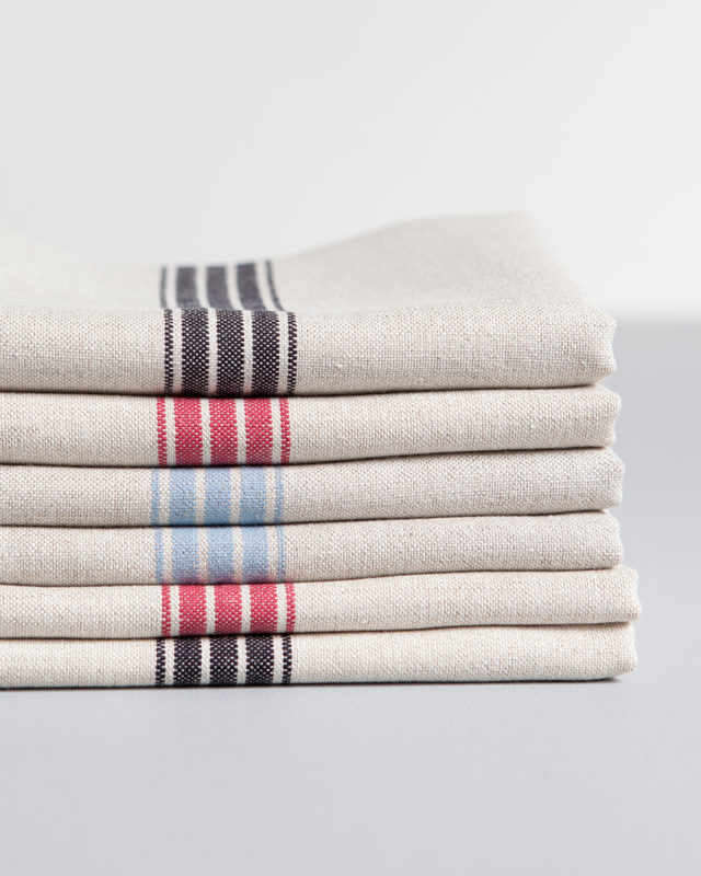 Stack of Mungo provincial stripe napkins woven from cotton and linen with a colourful stripes, pictured here in french navy, red and bluebell
