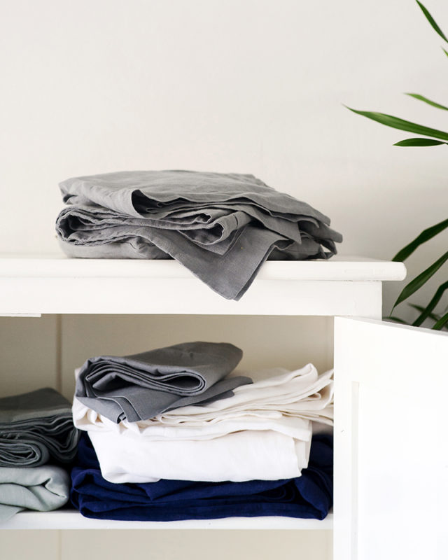 Mungo Kamma Linen in the linen cupboard at home in Bucatto Blue, Fumo Grey and Cripst white. 100% linen woven in South Africa