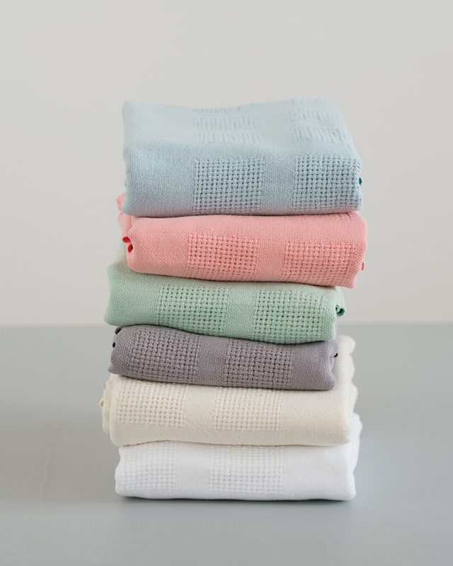 Pile of organic cotton cot baby blankets woven by Mungo
