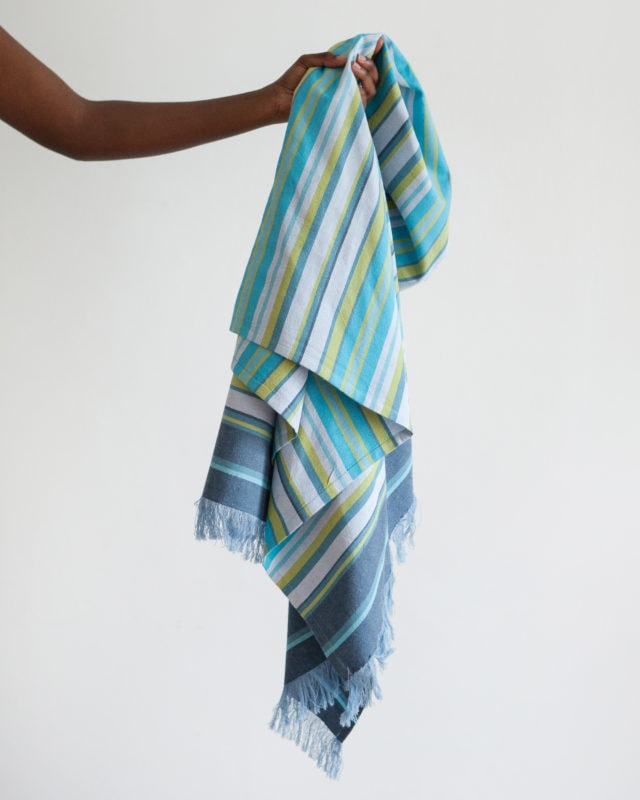 The Mungo 100% Cotton Kikoy South can be used as a versatile beach wrap or sarong shown here in our blue Capri colour